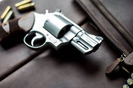 .44 magnum revolver handgun with bullet on leather background Imagens