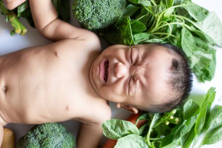 Baby kid boy lying cry with various of vegetable on white Stockfoto - 132097358
