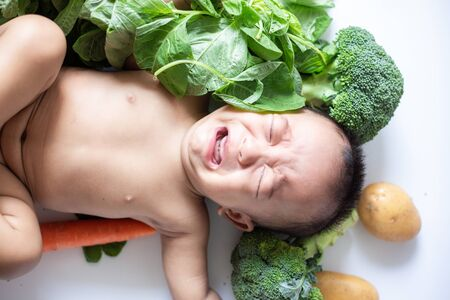 Baby kid boy lying cry with various of vegetable on white Stock Photo