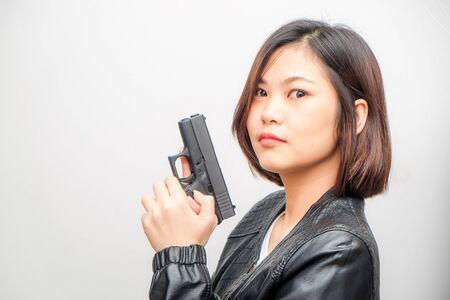 Hermosas mujeres inteligentes con pistón de pistola semiautomática sobre fondo blanco.
