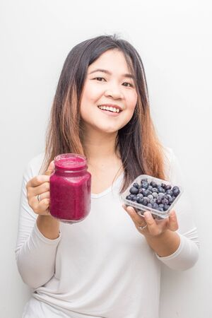 Asian wellnes women with blue berry smoothies summer drink on white background Foto de archivo
