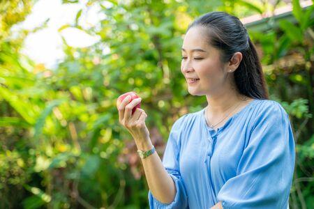 Porträt von schönen asiatischen Frauen mittleren Alters, die Apfel im Park halten, gesundes Konzept