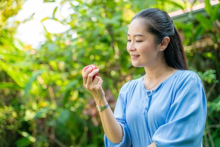 Portrait de belles femmes asiatiques d'âge moyen tenant une pomme dans un parc, concept sain