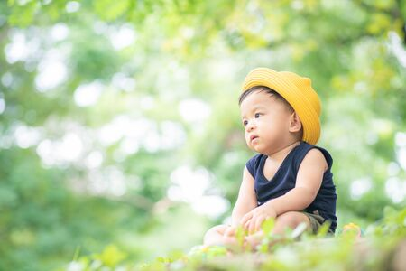 Kid boy with yellow hat travel in green city park toddler boy in nature
