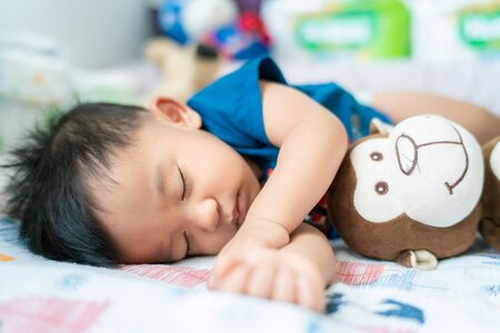 Cute infant asian baby boy sleep on blanket day time, Health care concept