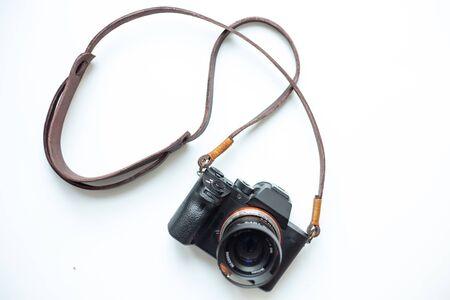 Sangle d'appareil photo en cuir véritable faite à la main avec appareil photo sans miroir sur fond blanc