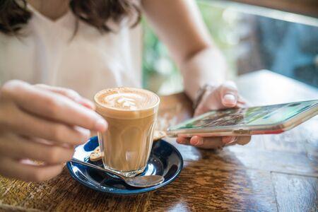 Women hand use smartphone in cafe shop, Cloe sup blank screen Banco de Imagens