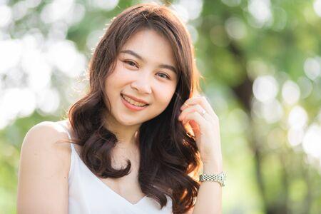 Portrait of smiling beautiful asian women in park morning light with bokeh half body portrait