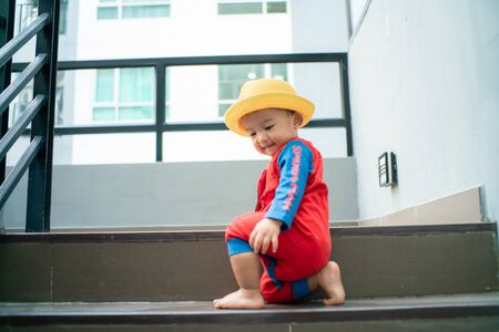 Funny baby boy crawling climbs up stair, Baby development Stock fotó