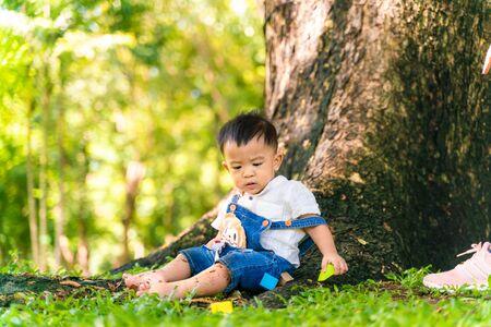 Infant asian baby boy sitting in city park sunny day under tree children development