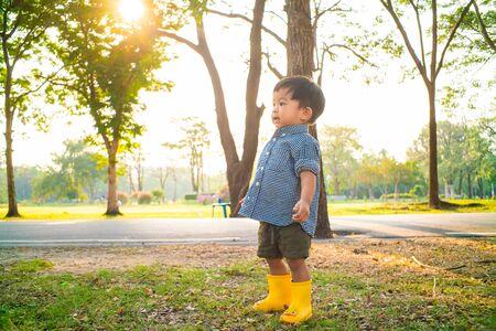 Petit garçon asiatique essaie de marcher sur l'herbe verte dans la lumière du coucher du soleil du parc public, bébé garçon dans le parc