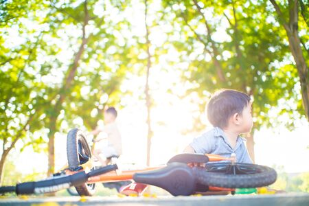 Asian boy falling balance bike accident on road in park tree forest outdoor activity