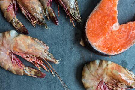 Fresh salmon fish with sea prawn shrimp on black plate, Seafood Foto de archivo