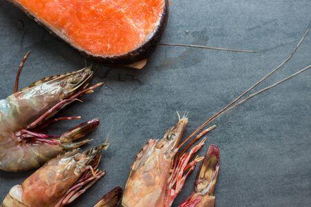 Fresh salmon fish with sea prawn shrimp on black plate, Seafood