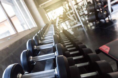 Fila de pesas grandes en el estante en el moderno gimnasio deportivo de cerca Foto de archivo