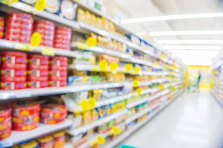 Abstract blurred modern supermarket with many various goods people shopping