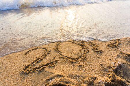 Number 2019 sign on sand beach wave sunset light background Standard-Bild - 142147519