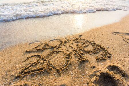 Number 2019 sign on sand beach wave sunset light background Standard-Bild - 142147768