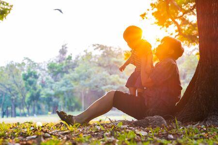 Ältere ältere Großmutter, die mit Enkelkind unter Baum im Stadtpark spielt Sonnenunterganglichtkraft des Hochgefühlskonzepts Standard-Bild