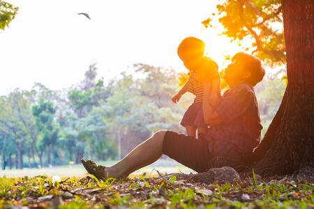 Senior elderly Grandmother Playing with grandson baby boy under tree in city park sunset light power of elationship concept Imagens