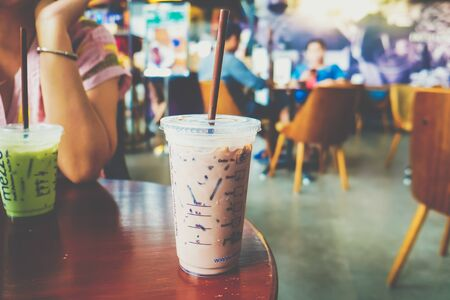Ice coffee cup on wooden table in modern cafe blurred people background
