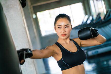 Atractiva mujer asiática perforando una bolsa negra con guantes de boxeo en el gimnasio, kickboxing