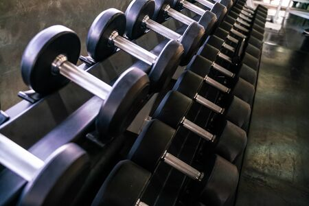 Dumbbell weight lift on roll in sport gym healthy concept