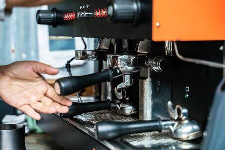 Prepares espresso machine brewing a coffee in coffee shop close up