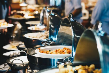 Crowd of people enjoying buffet food meal dining Food Options Eating Concept in hotel buffet Banco de Imagens