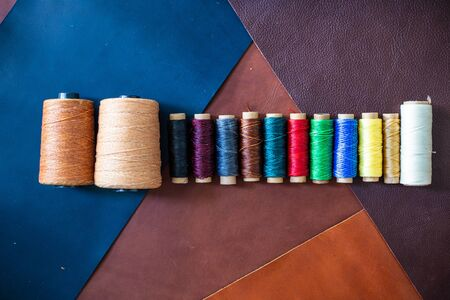 Colorful linin wax thread on leather background craftmanship working industry Stock fotó