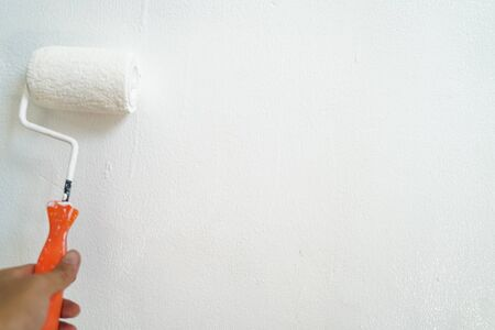 Hand paint white color roller on house wall maintenance, Renovate concept