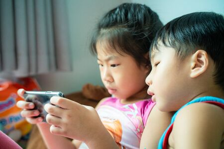 Children friend girls and boy group playing internet with mobile smartphone in room, Child With Cellphone