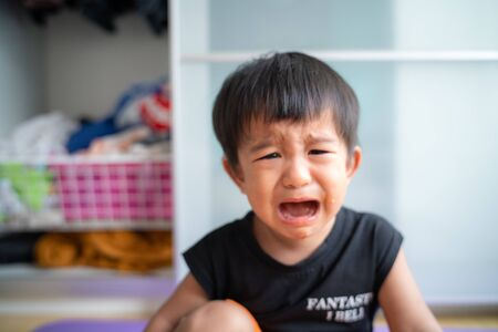 Little asian boy crying bitterly in room of house facial face mood