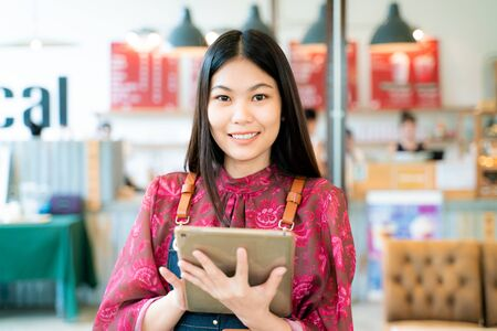 Beautiful entrepreneur asian woman with long hairstyle holding digital tablet while standing in the doorway of her coffee shop