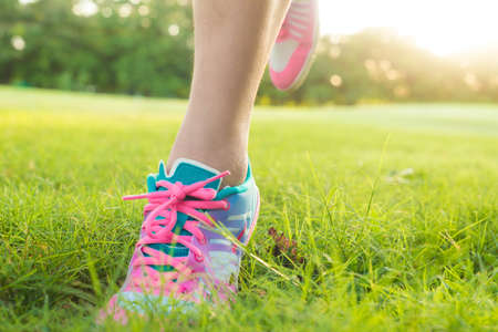 Foot of sport women running on green grass field in oark with sun light close up on shoe