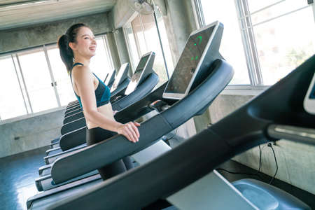 Asian woman jogging on a treadmill working out in gym, Cardio exercise