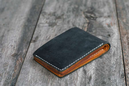 Black leather bifold money and card wallet on wood crafts working