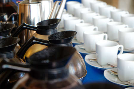 Coffee cup on table with coffee pouring from jar business food and drink