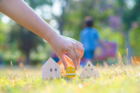 Hand choose wooden house on green grass saving concept for buying a home idea of investment funds