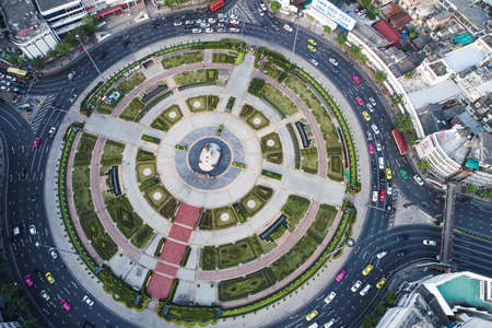 Aerial view vehicle on circular junction road with city building transport industry