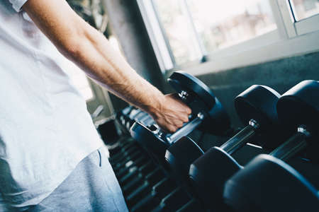 Smart sport man lifting dumbbell up in fitness gym wellnes activity hand close up