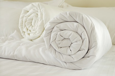 羽毛布団に孤立した白い背景を重ね合わせて塗りつぶされた布団をロールダウンします。