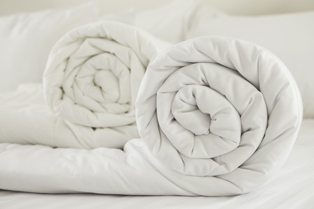 Duvet roll  down filled duvet rolled up isolated on white background Banco de Imagens