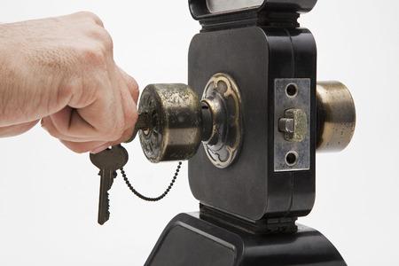 Hand hold a key in Aluminium door knob on the black door white background. photo