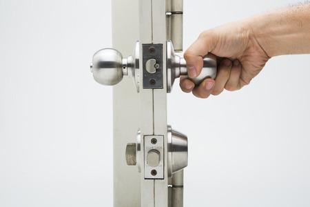 tocar la puerta: Asimiento de la mano un pomo de puerta, fondo blanco puerta de aluminio. Foto de archivo