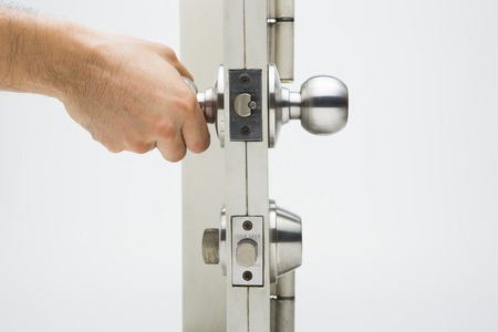 cardkey: hand hold a Door knob, aluminum door white background. Stock Photo