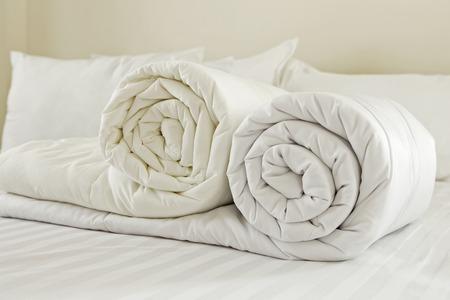 羽毛布団のロール。下の孤立した白い背景の重ね布団をいっぱい