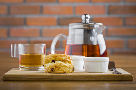 breakfast table with tea, teapot, cup of tea, jam, bread and honey photo