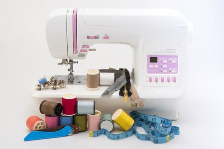 maquina de coser: Fondo con herramientas de costura y tejido de color Foto de archivo