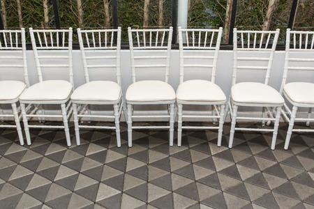 arched: White chairs arranged in rows Stock Photo